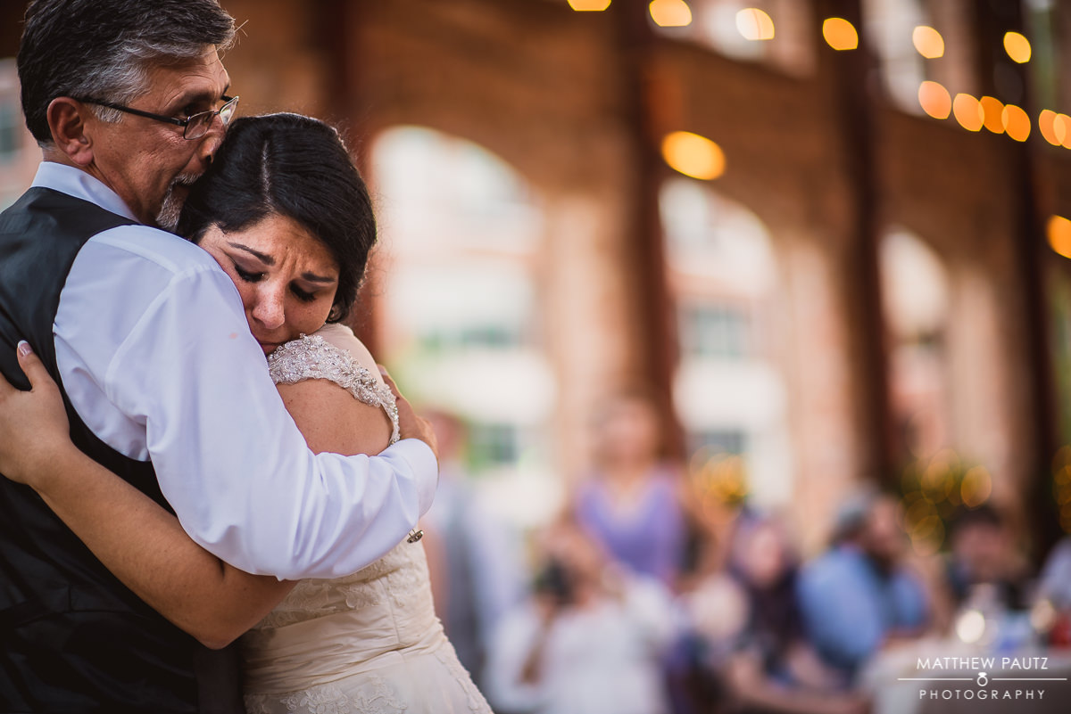 tearful bride dancing with father at reception