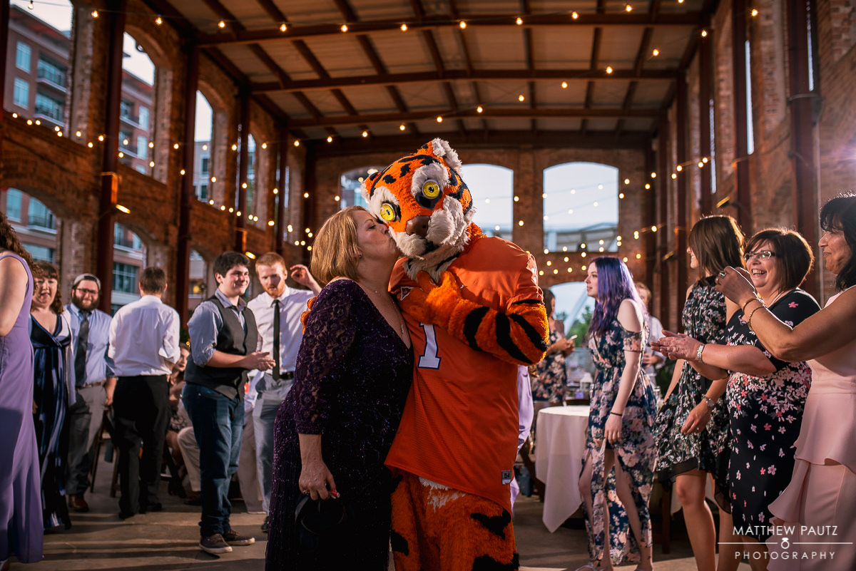 Wedding guest kissing Clemson Tiger at wedding reception