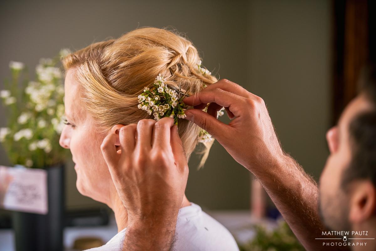 bride having flowers put in her hair before wedding ceremony