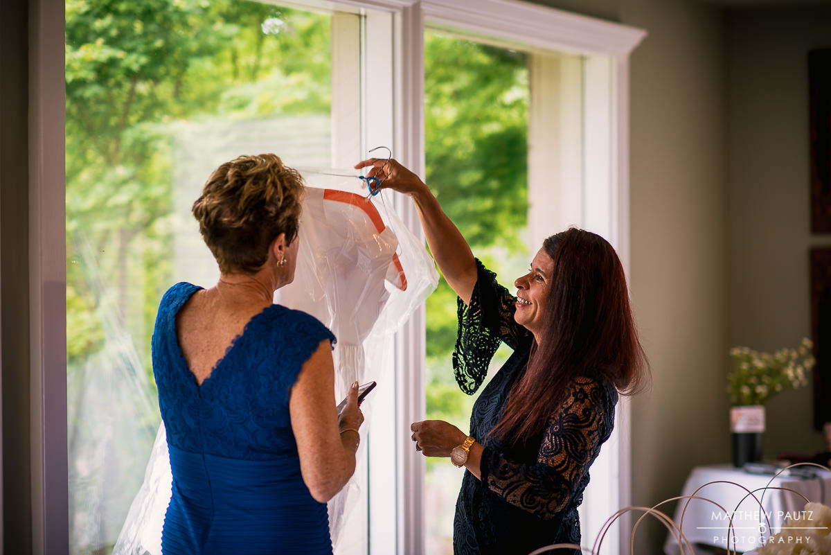 mother of bride grabbing wedding dress down from the window