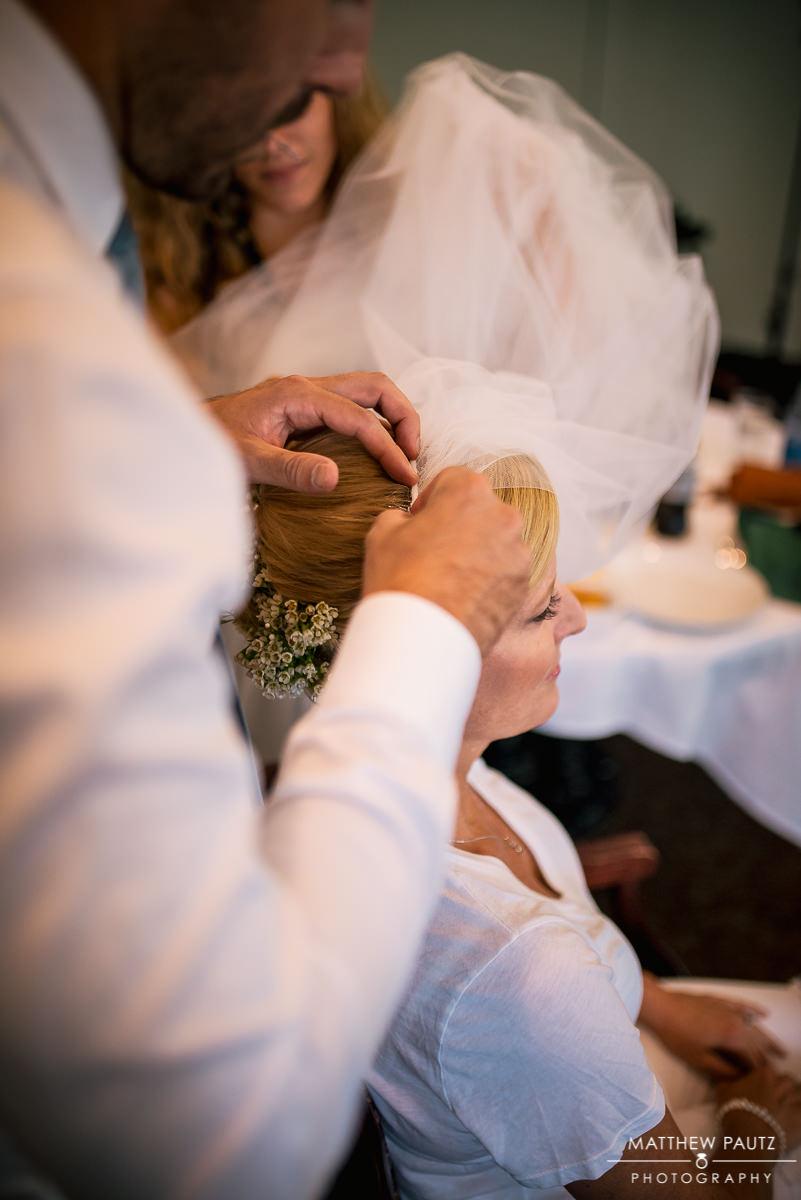 bride having veil put in before wedding ceremony