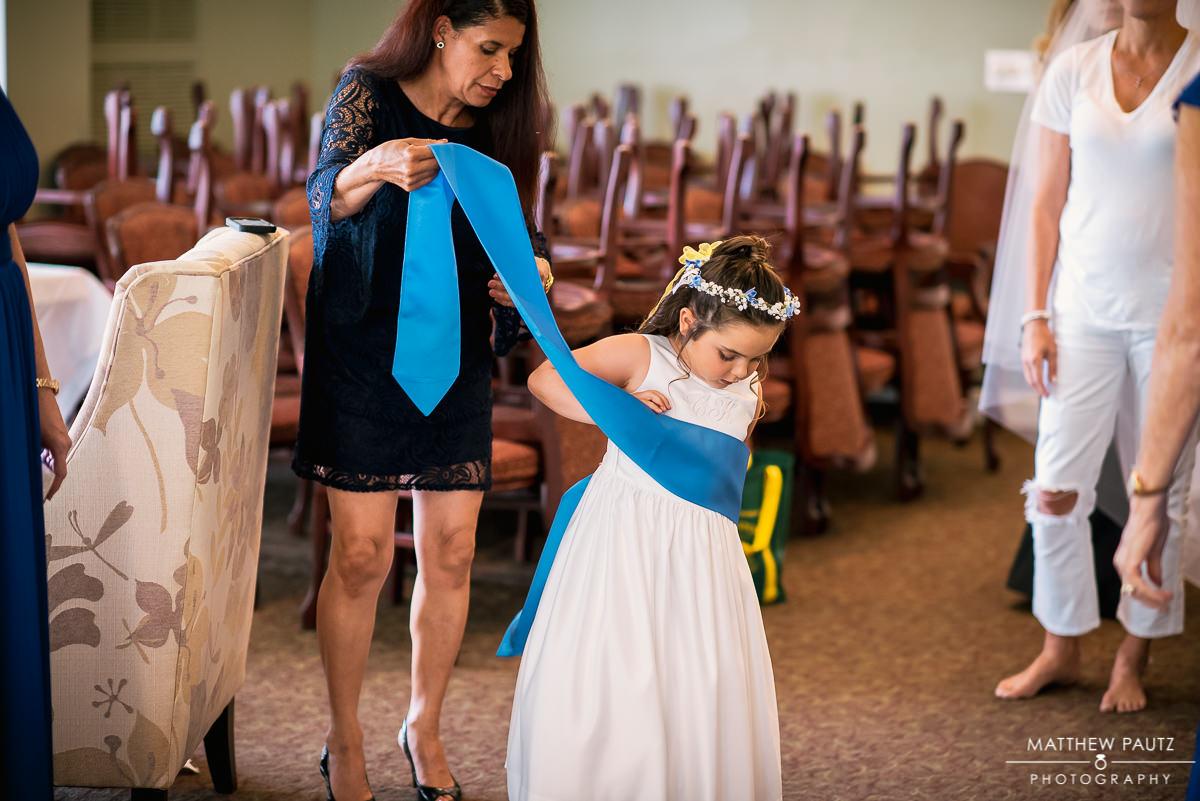 flower girl having sash put on dress