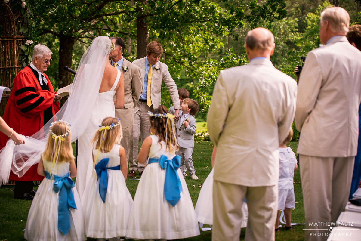 ring bearer acting out during outdoor wedding ceremony