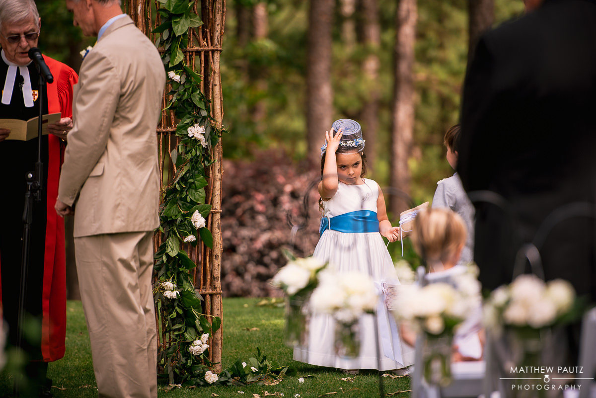 flower girl with bucket on head during wedding ceremony