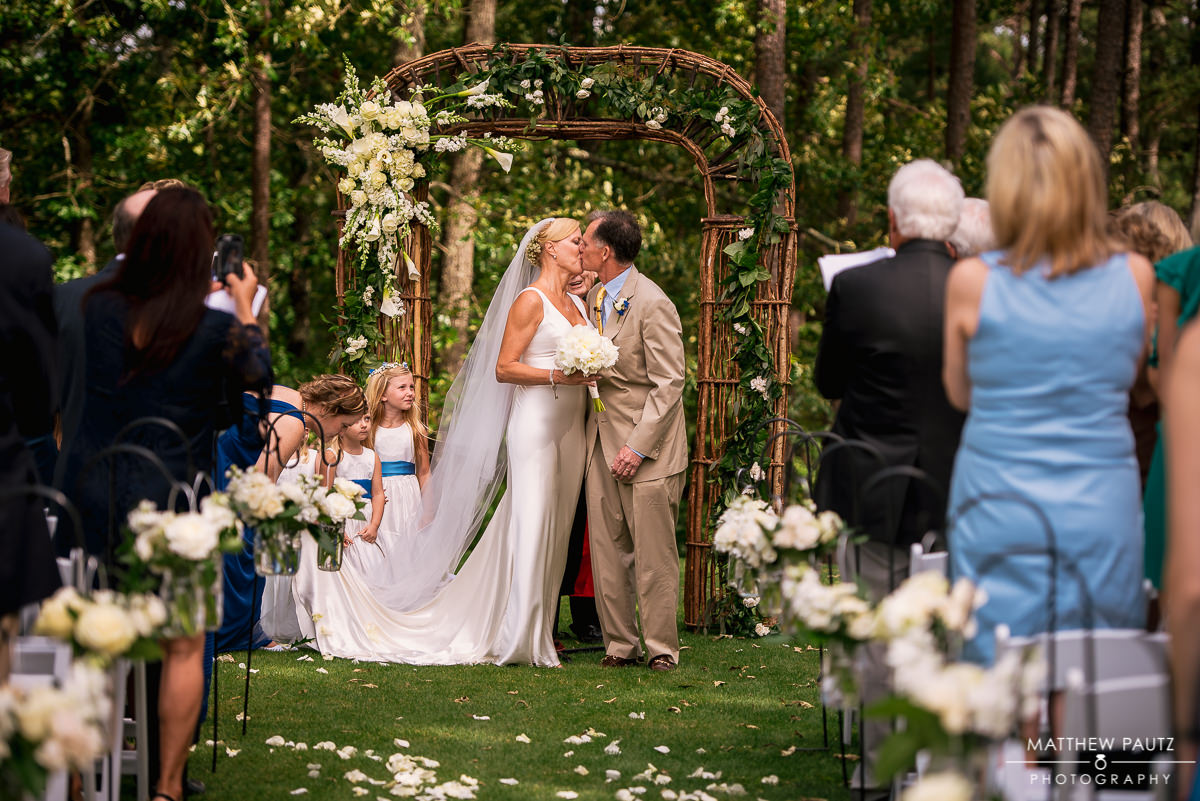 wedding couple first kiss at outdoor ceremony