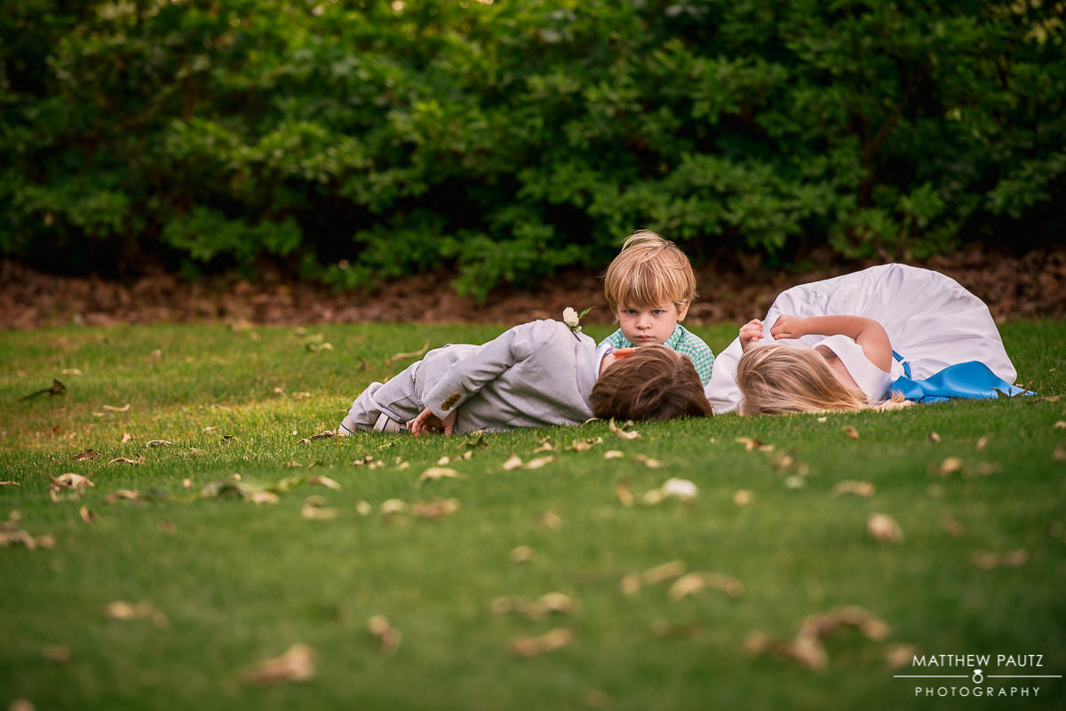 wedding children rolling around in grass after wedding ceremony