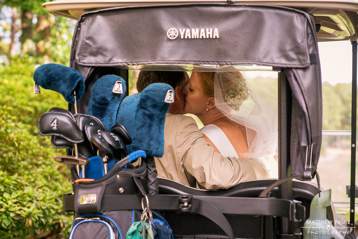 bride and groom kissing in golf cart at country club