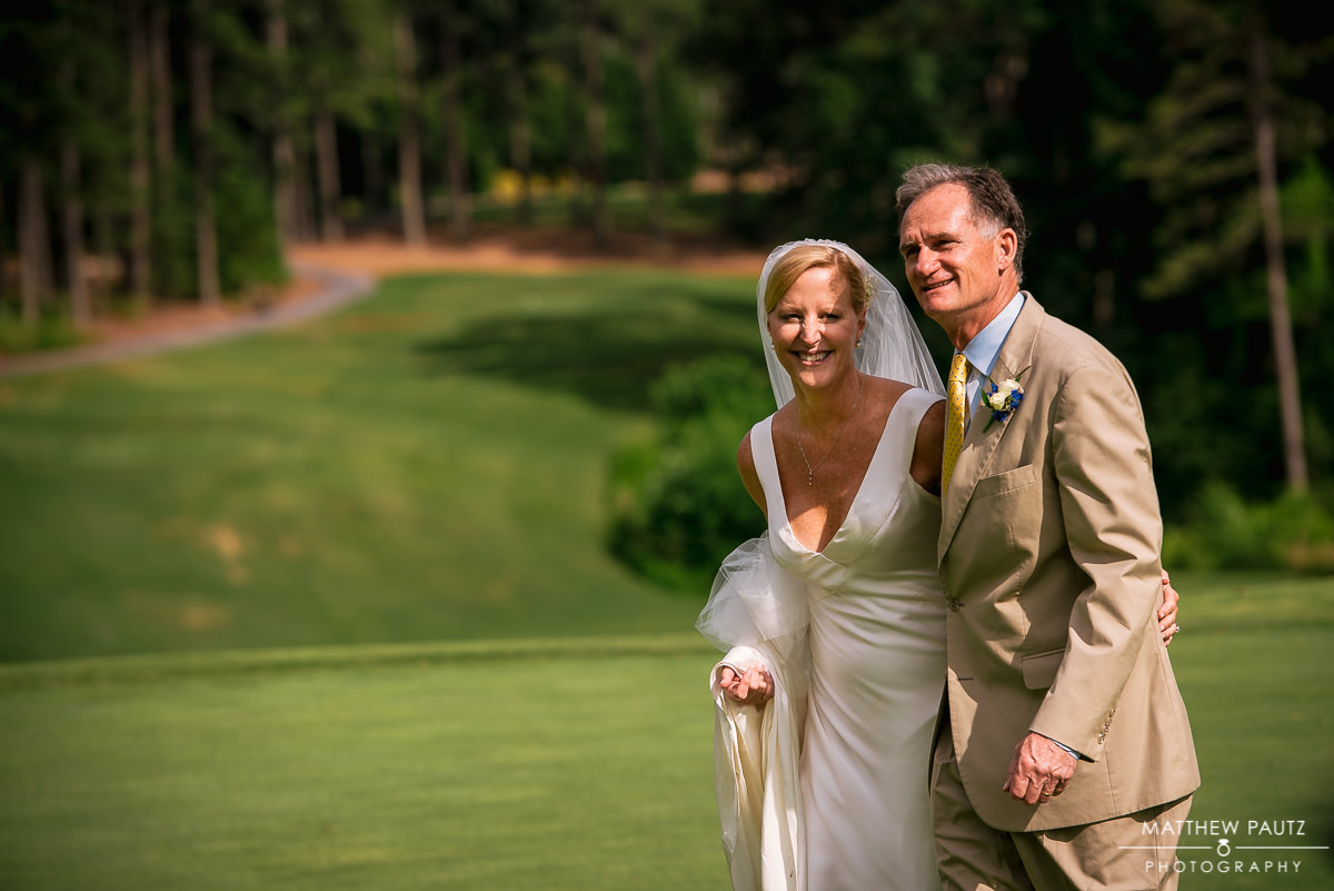 newlywed couple posing for photos on golf course at country club