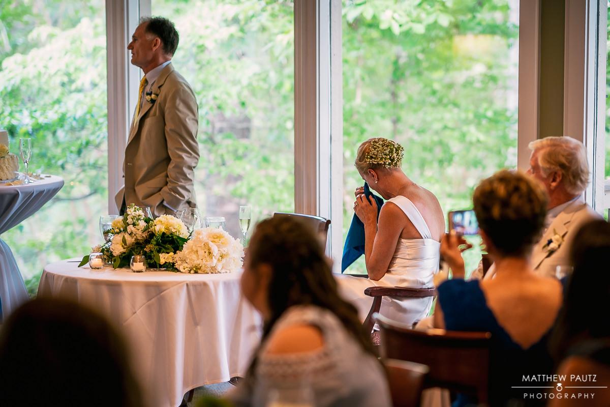 bride crying while new husband gives toast at wedding reception