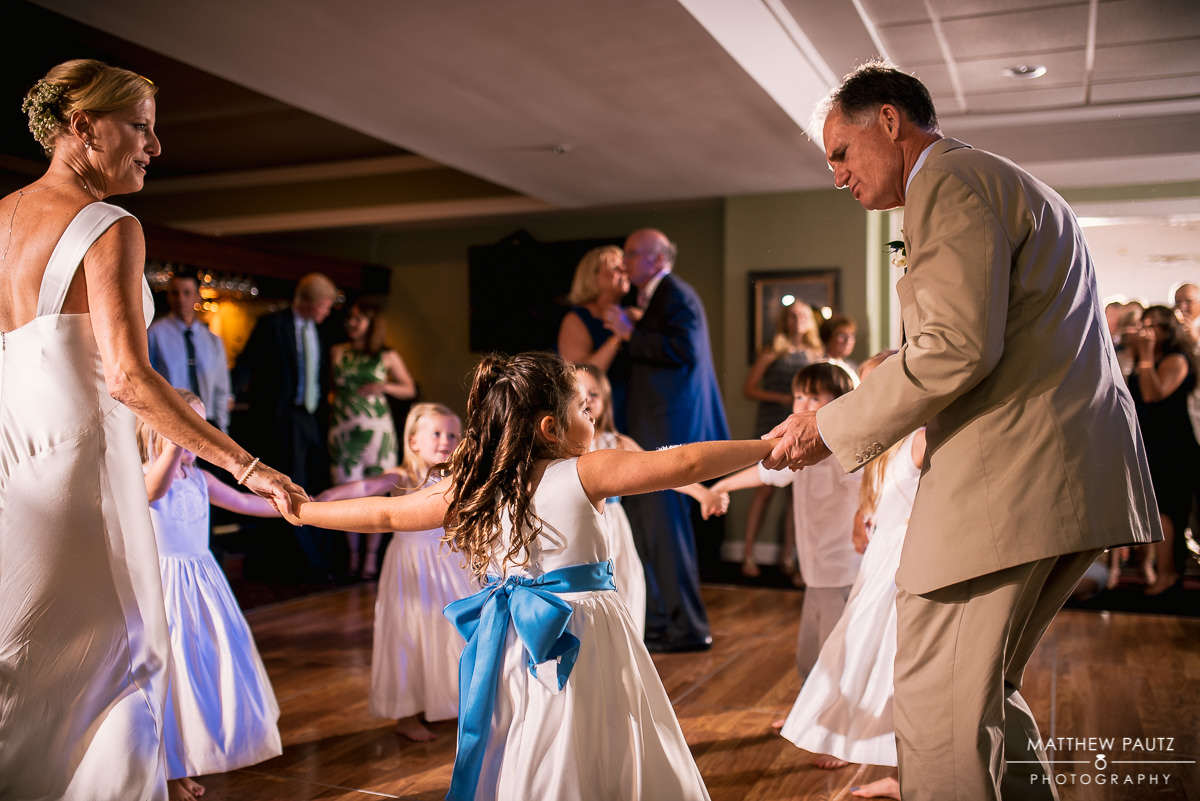 bride and groom dancing with flower girl at their reception