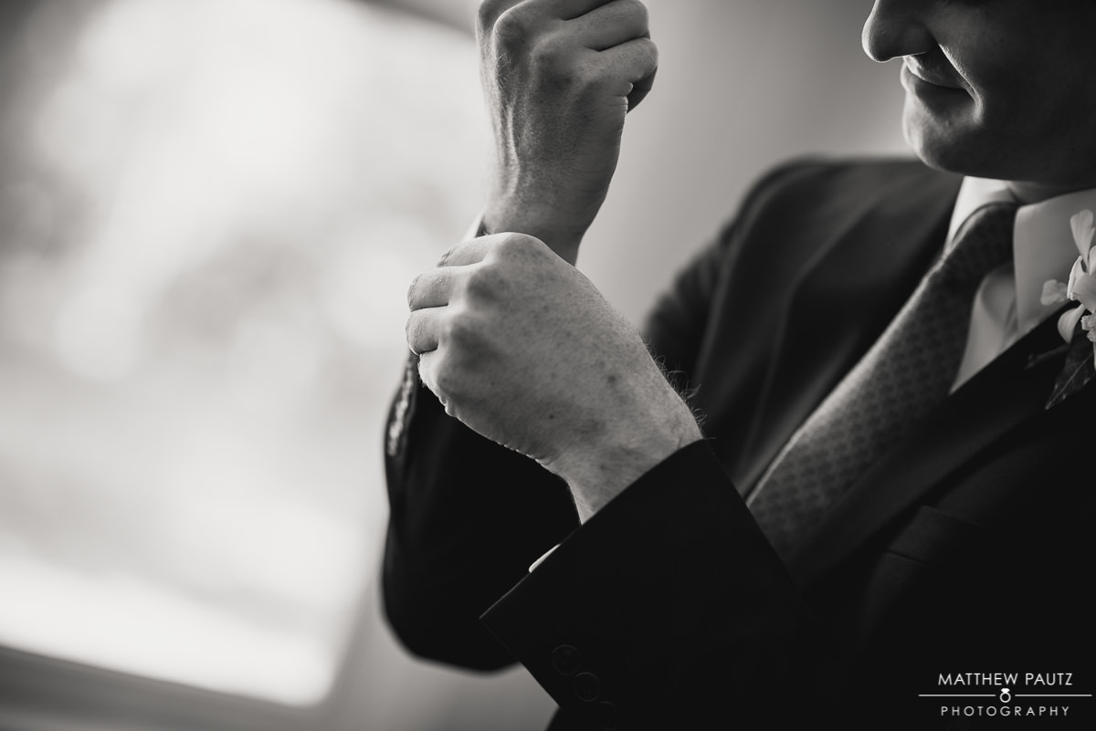 groom adjusting his cuffs before wedding ceremony