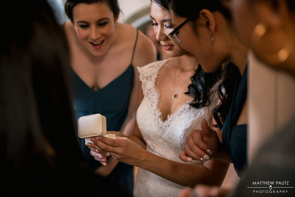 Bride showing off wedding ring in box to bridesmaids
