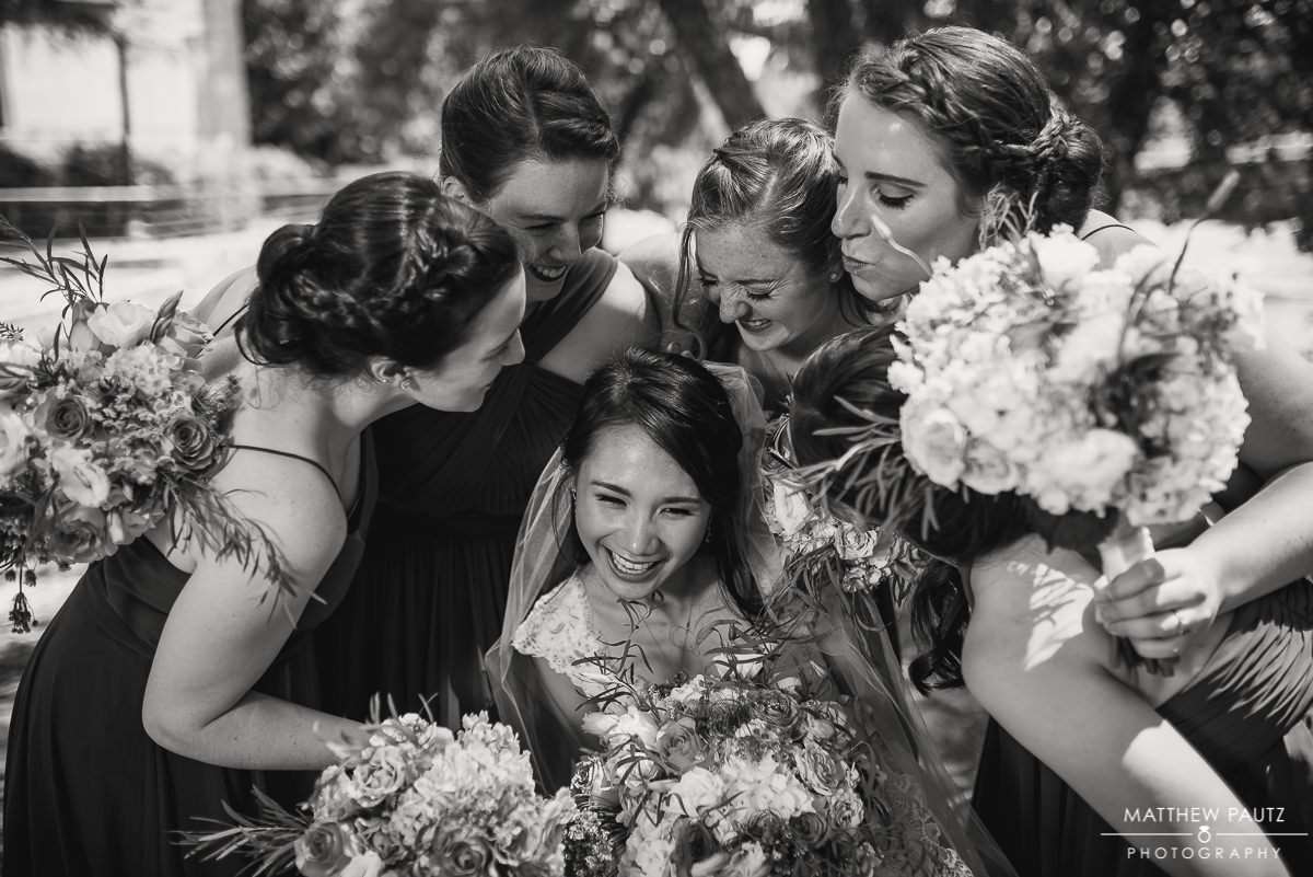 bride ducking from bridesmaids in group photo
