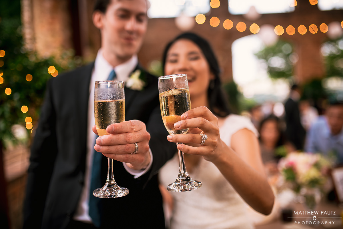 Bride and groom holding champagne glasses out in front of each other