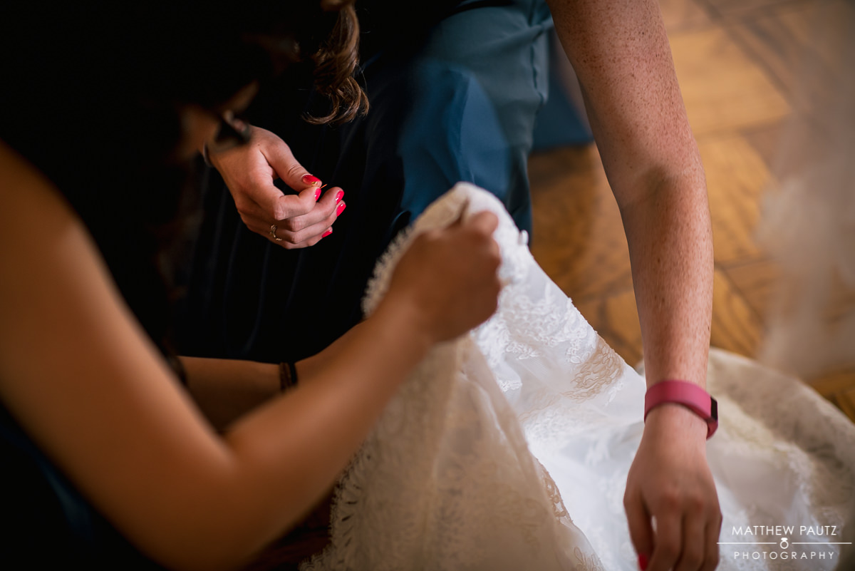 bridesmaids making last minute alterations to wedding dress