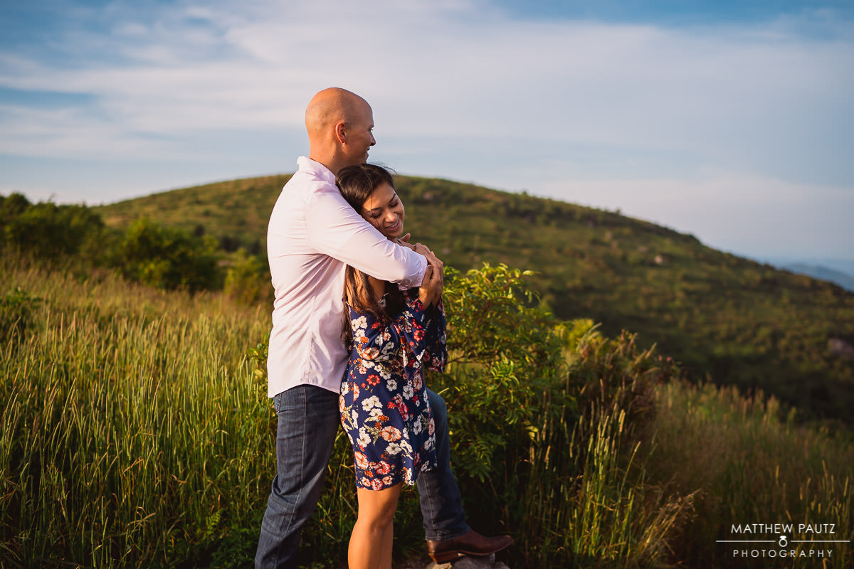 engaged couple hugging at sunset in blue ridge mountains