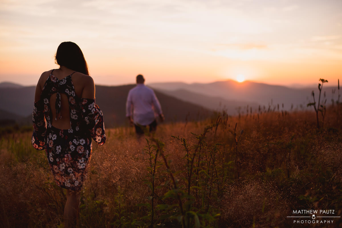 couple walking into the sunset on a mountain