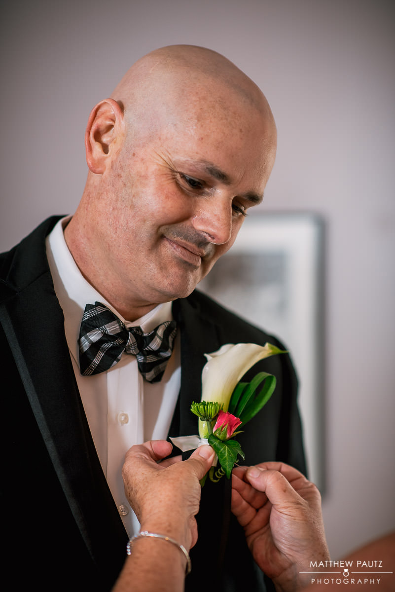 Groom smiling while getting ready for wedding