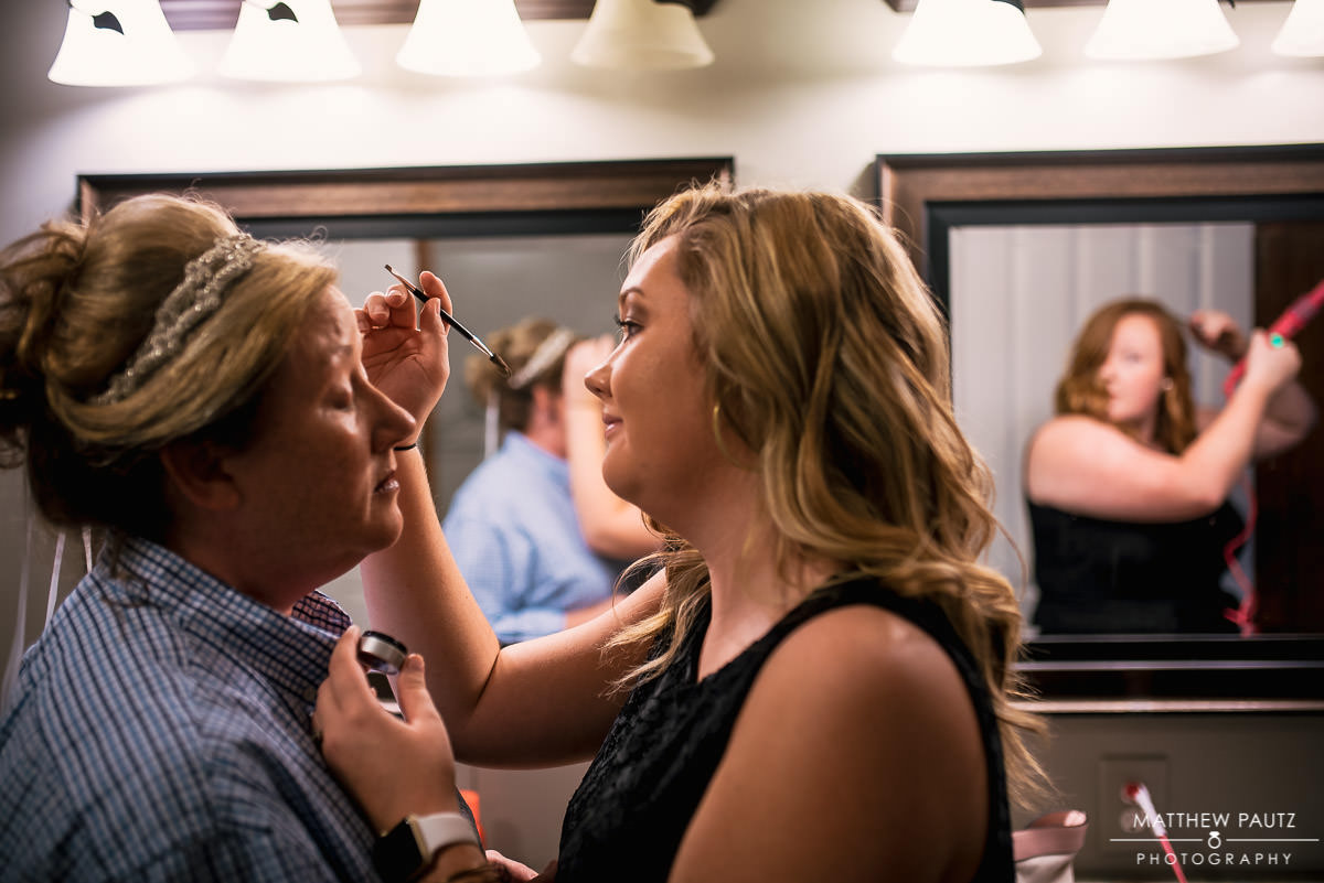 bride getting ready with daughter before wedding