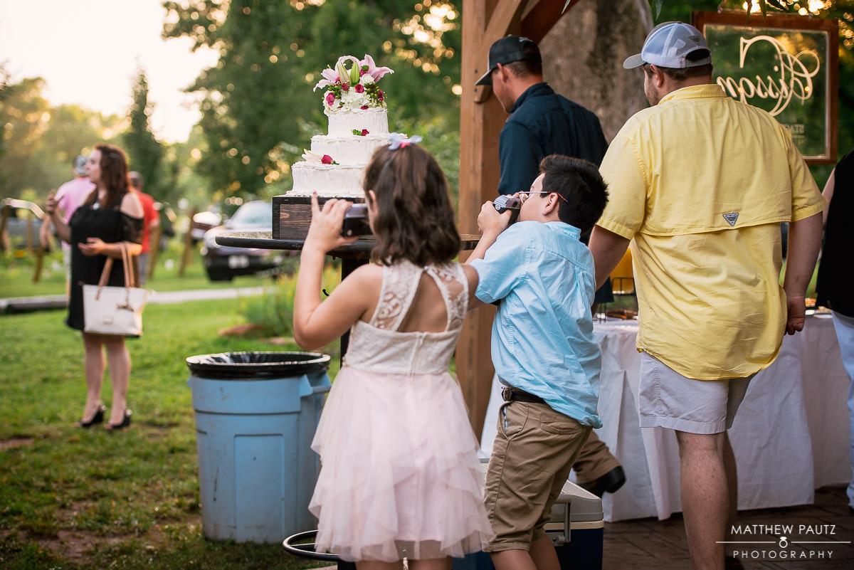 kids taking photos of wedding cake