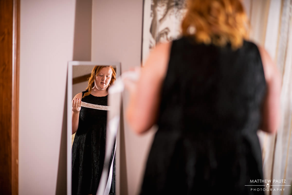 daughter of bride looking at herself in mirror