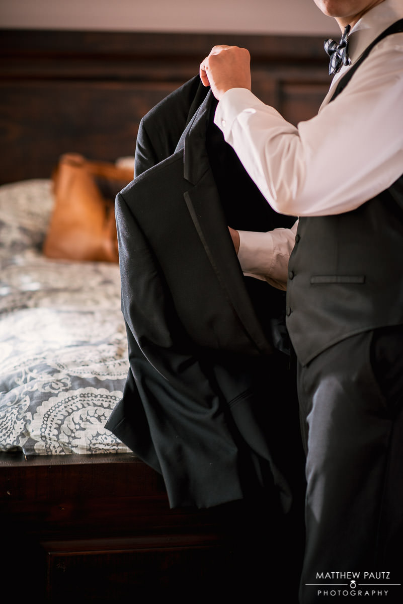 Groom putting on his jacket before wedding ceremony