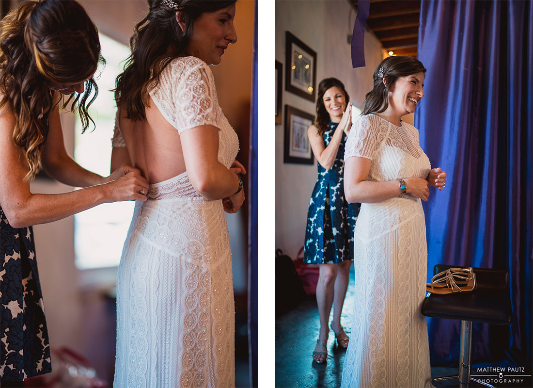 bride putting on her wedding dress with help from maid of honor