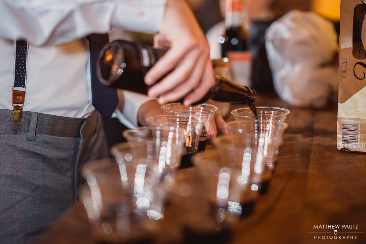 groomsman pouring shots of alcohol