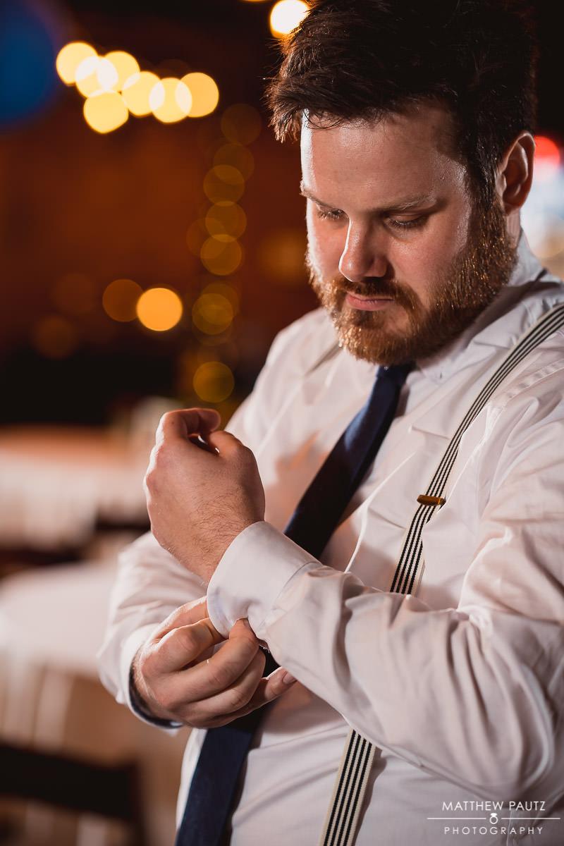 Groom adjusting cuffs before wedding