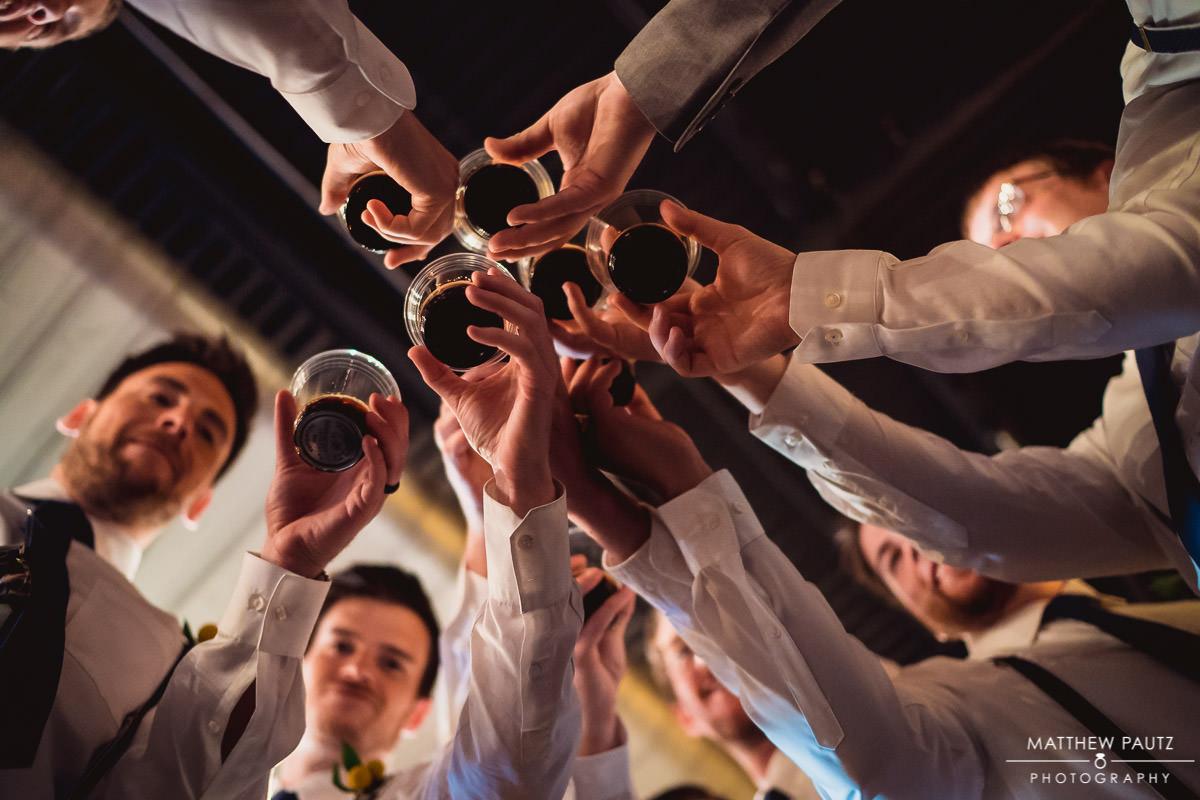 groomsmen taking shots of alcohol before wedding ceremony