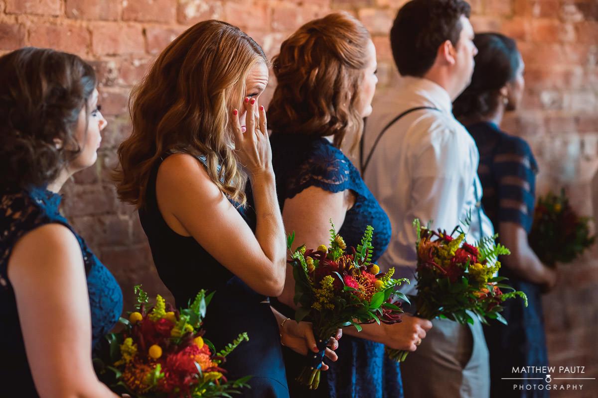bridesmaid crying at wedding ceremony at The Old Cigar Warehouse