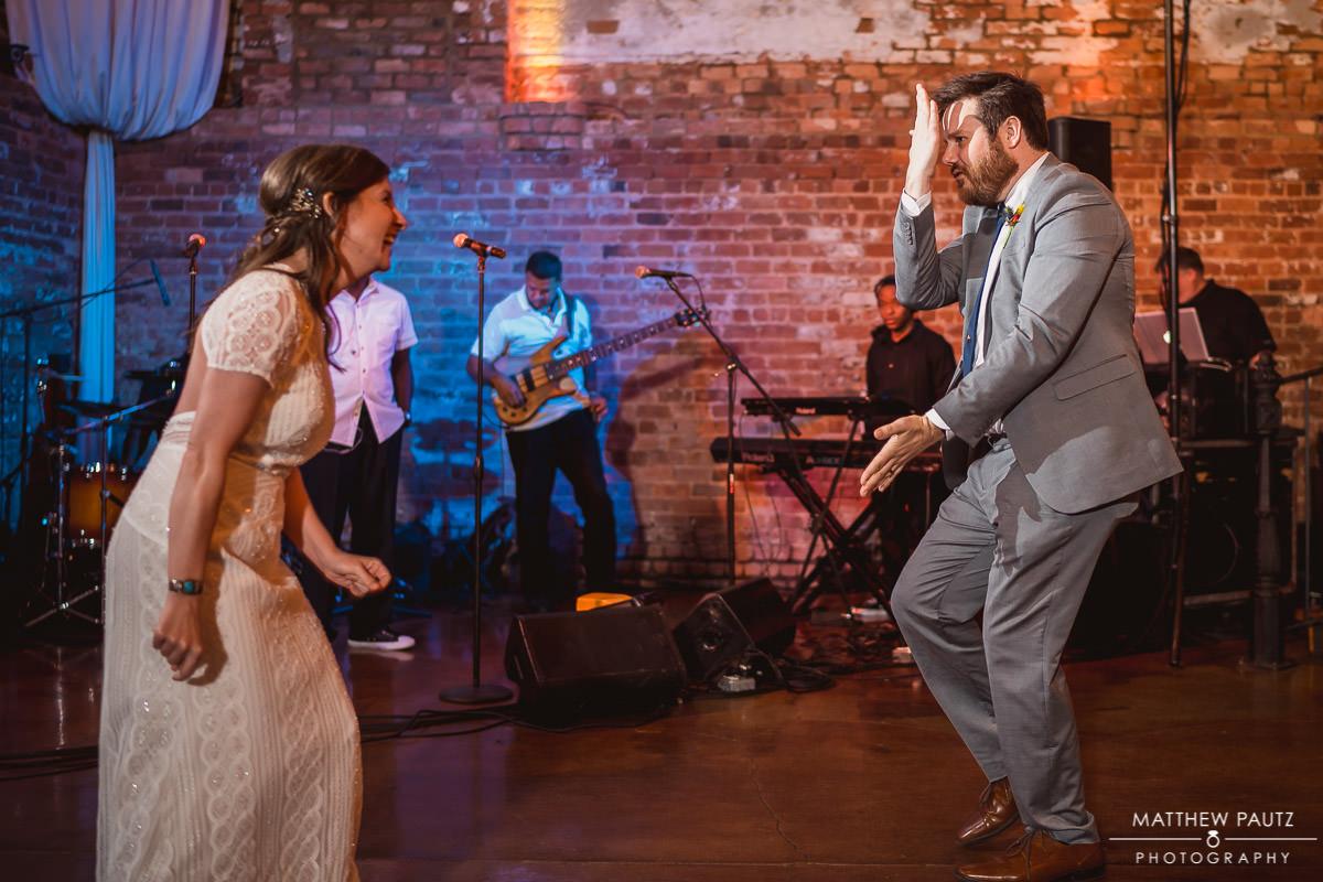 newlyweds dancing goofy at wedding reception