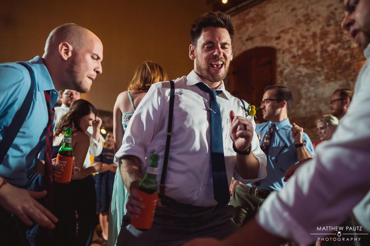 groomsmen having fun and dancing at reception
