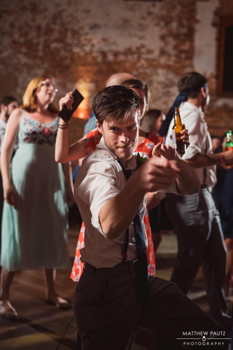 groomsman pointing at camera while dancing