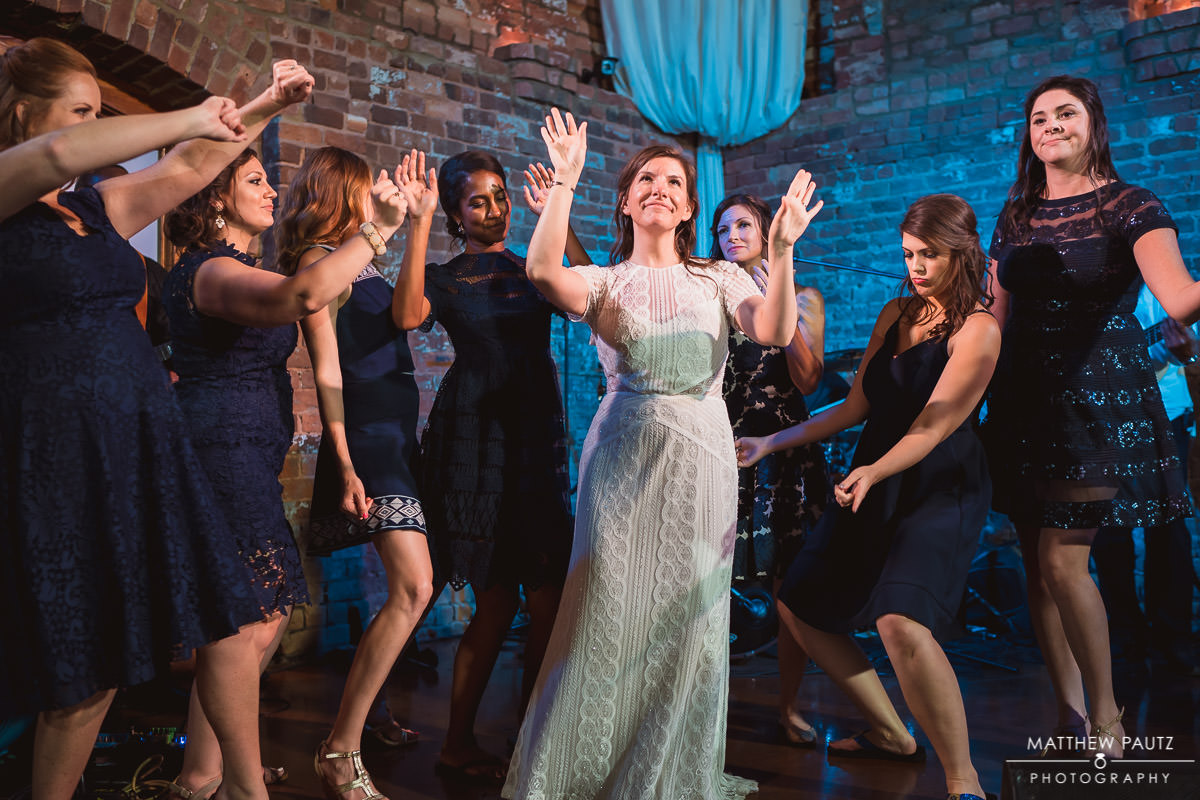 bride with bridal party on stage at reception