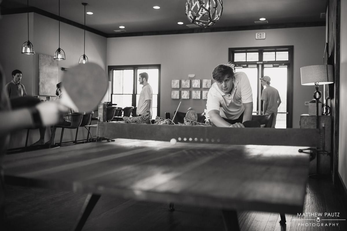 Groomsmen playing ping pong