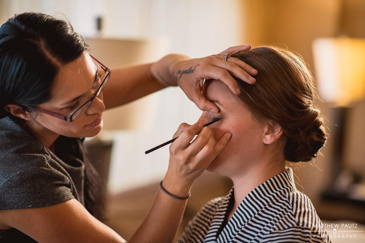 Bride having makeup done before wedding