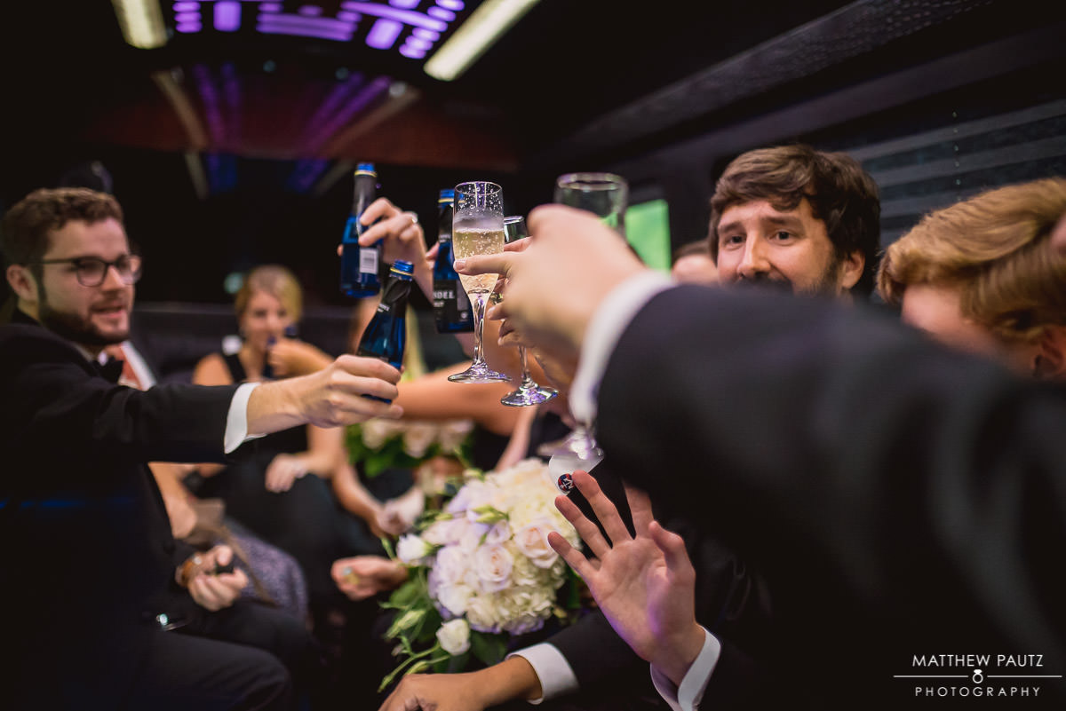 wedding party celebrating in limo after wedding