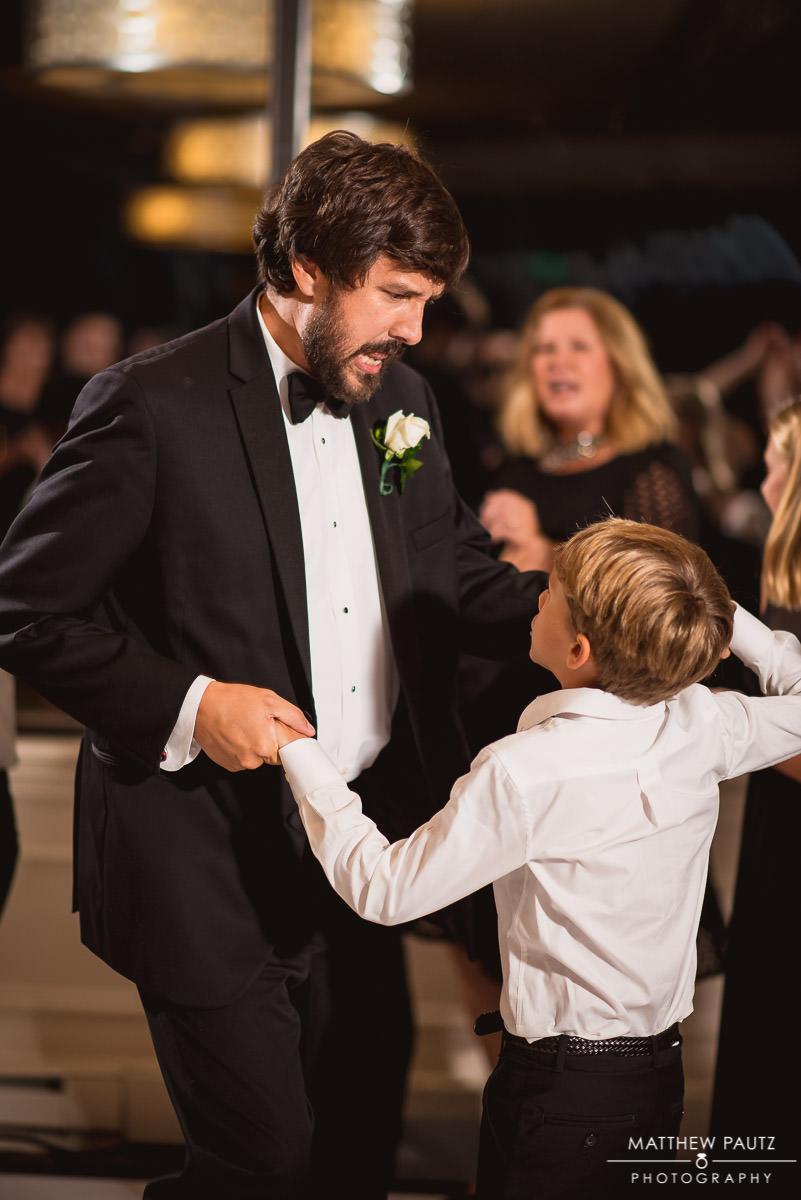 man dances with son at wedding reception