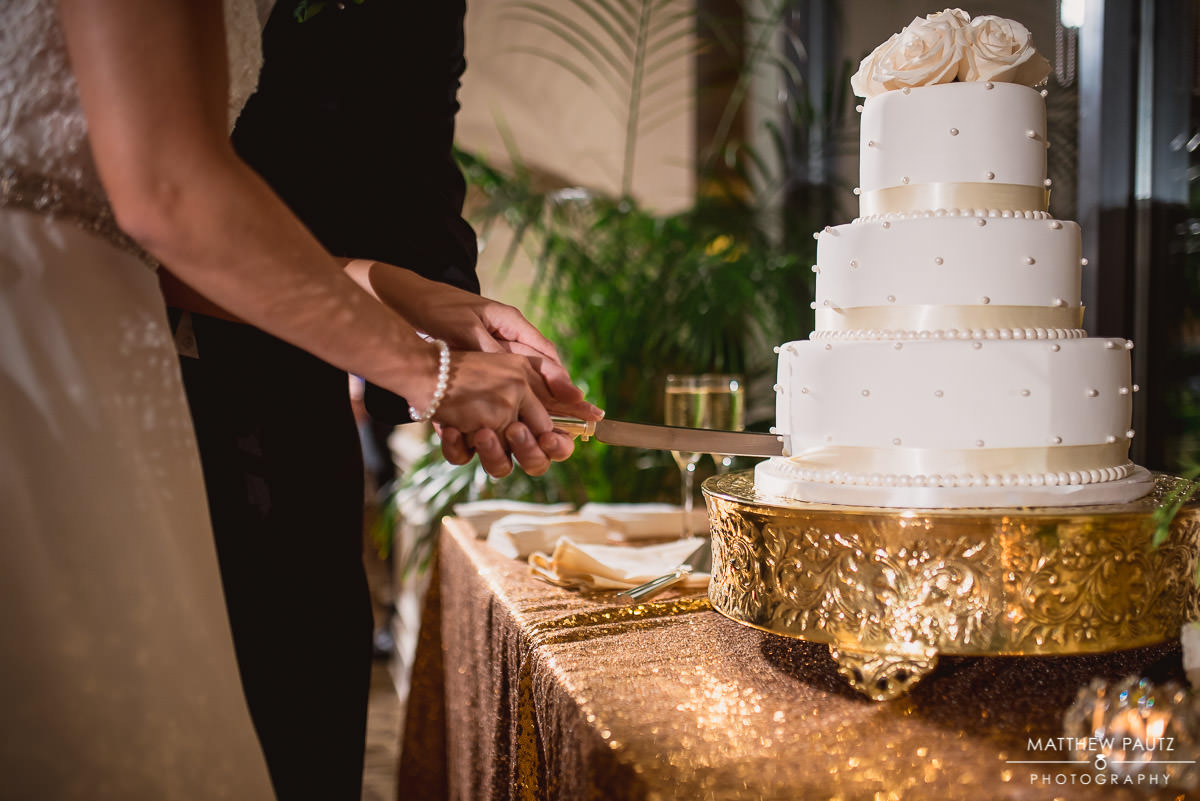 bride and groom cutting cake at wedding reception