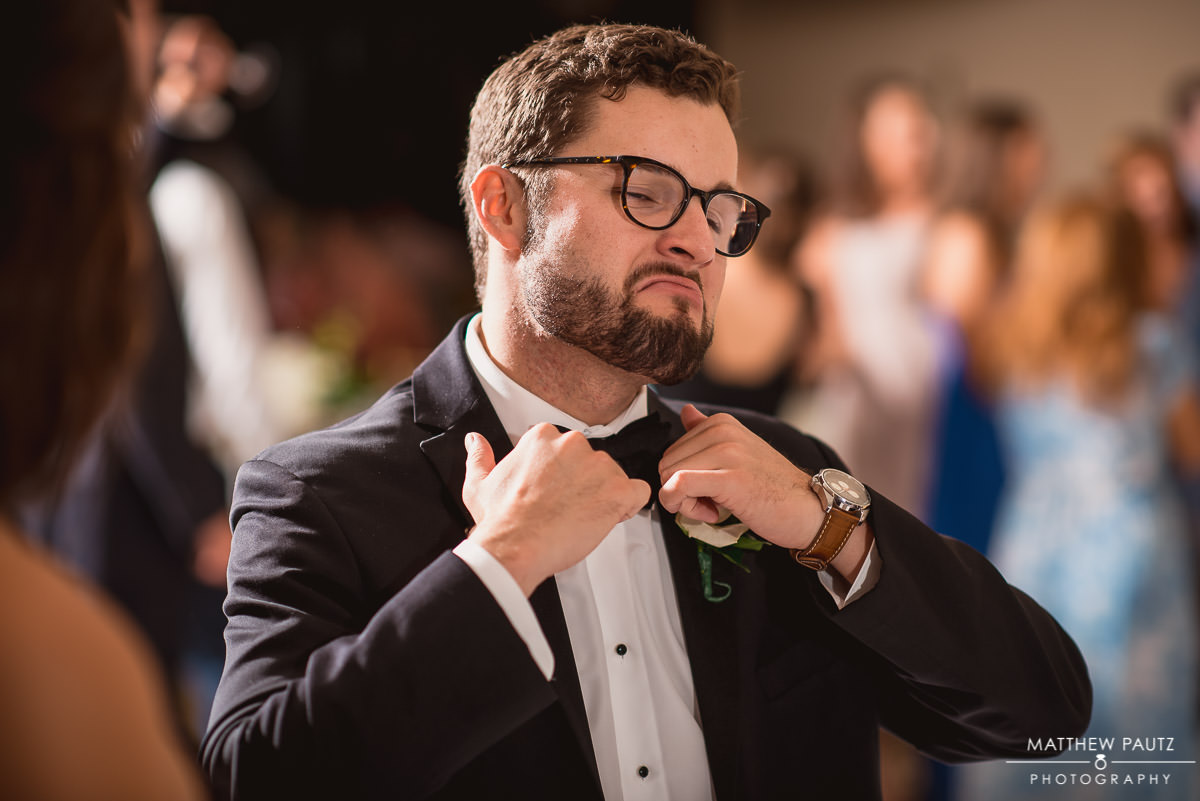 Funny groomsman dancing at wedding reception