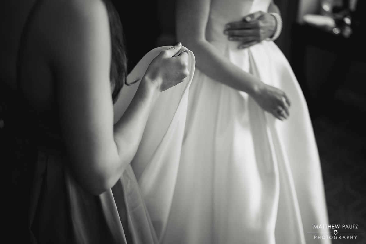 maid of honor helping bride put on wedding dress