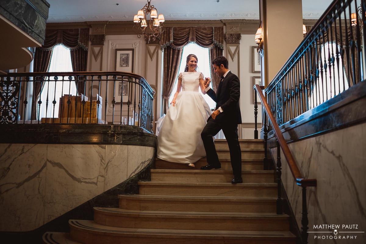 bride and groom walk down staircase together at The Westin Poinsett Hotel