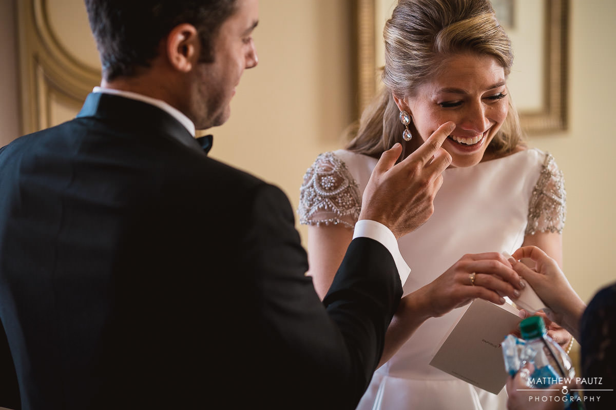 Groom wiping tears from bride's eye