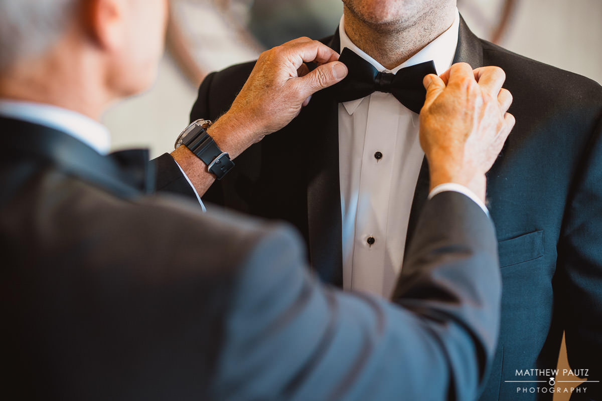 Father of groom adjusting the Groom's bowtie