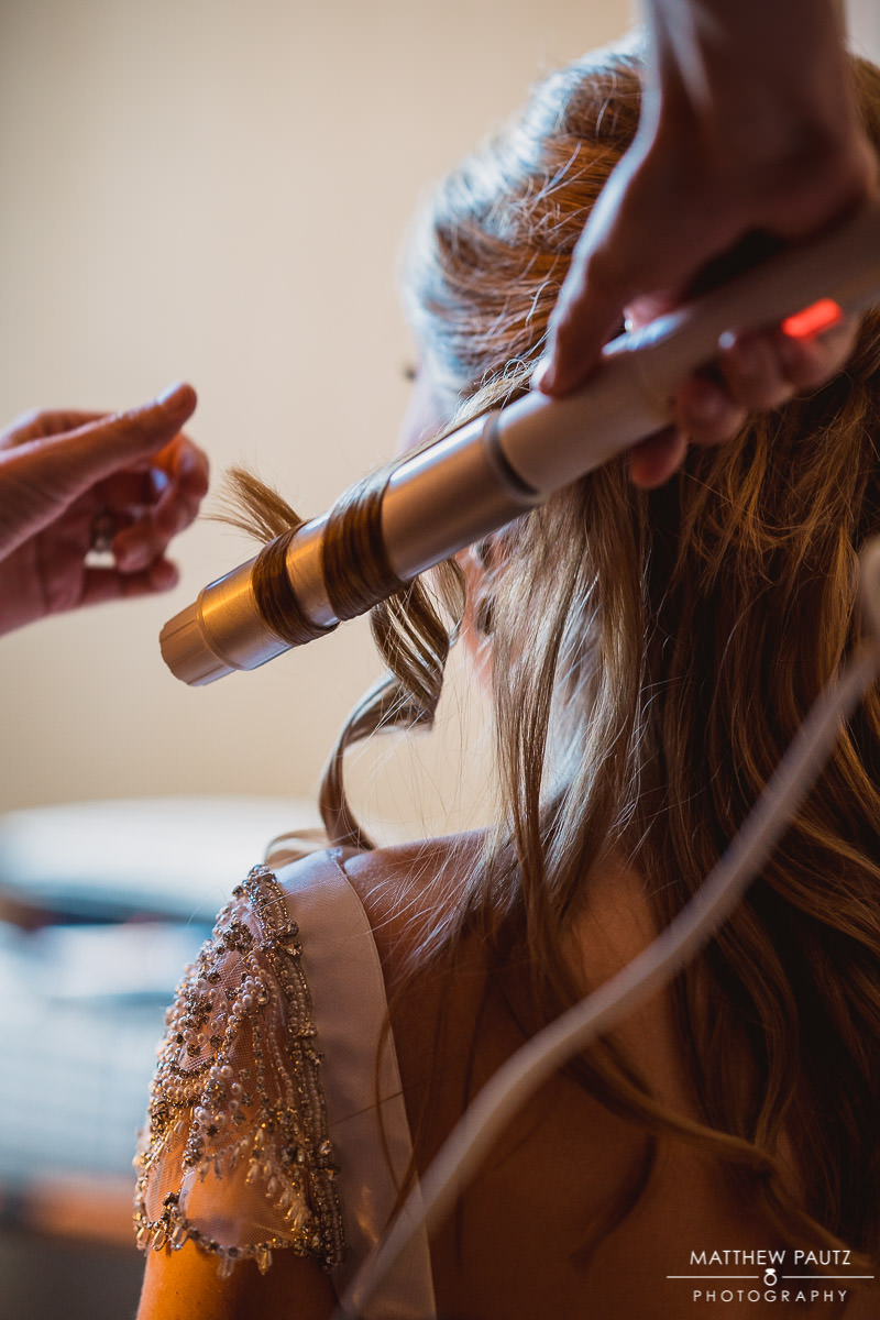 closeup of bride having her hair curled before wedding ceremony