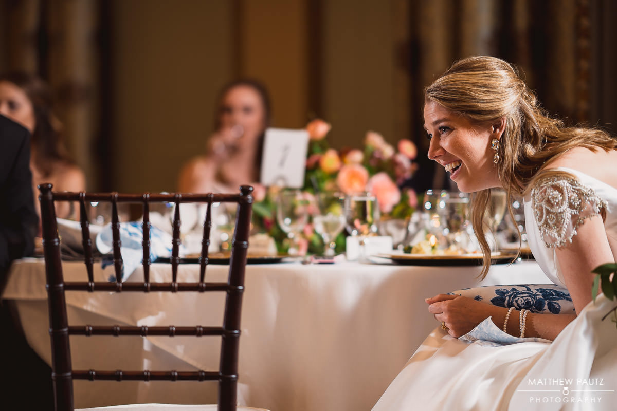 Bride leaned over and laughing during reception