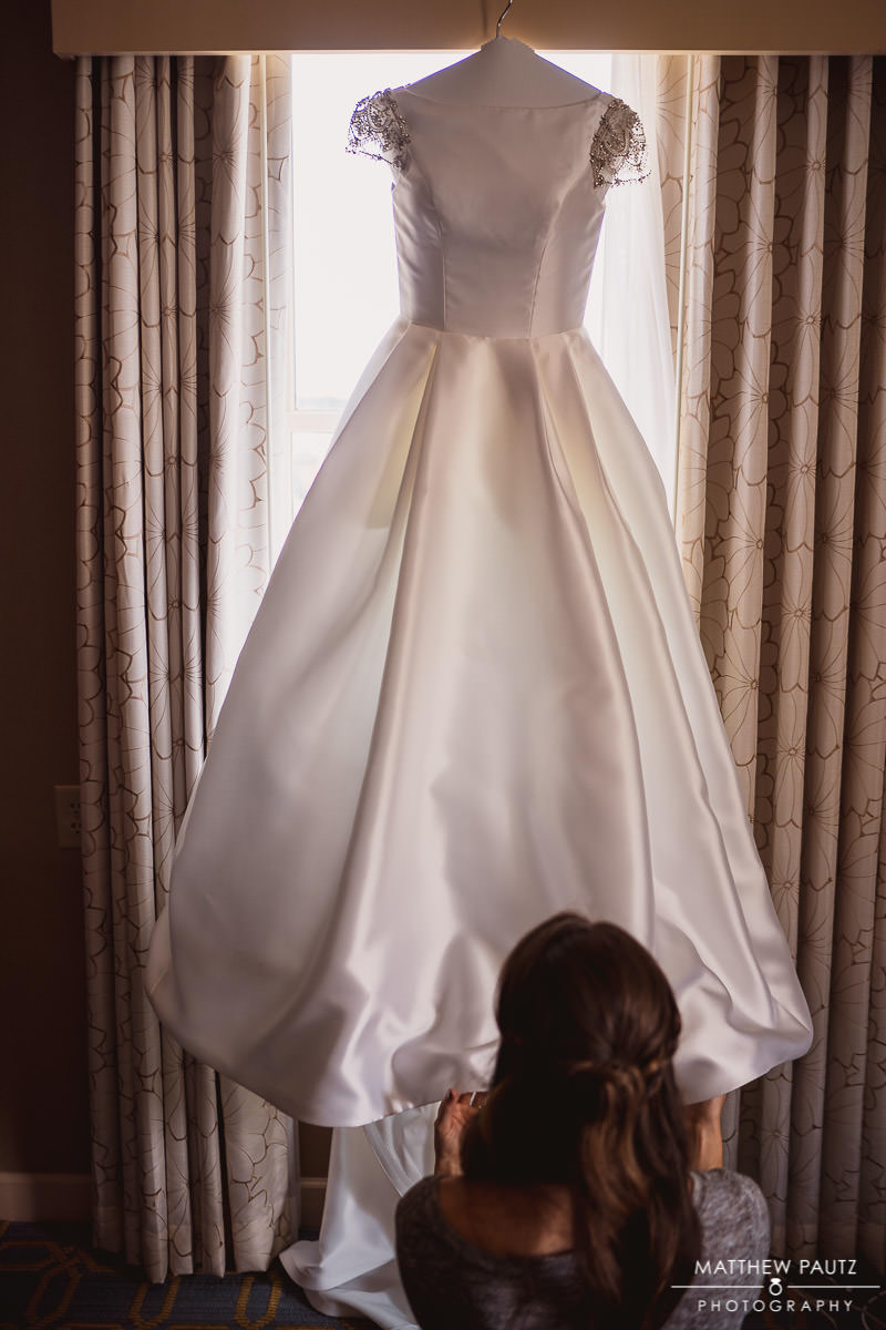maid of honor adjusting wedding dress before wedding