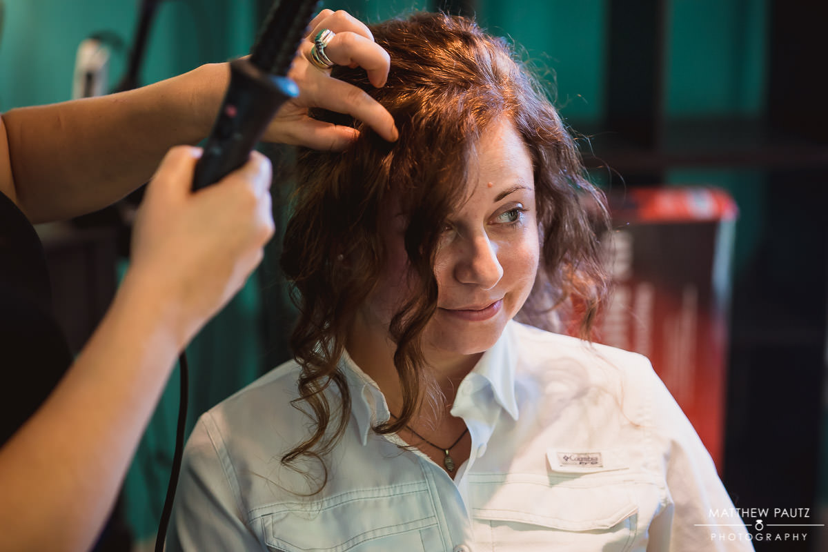A bride having her hair styled before destination wedding