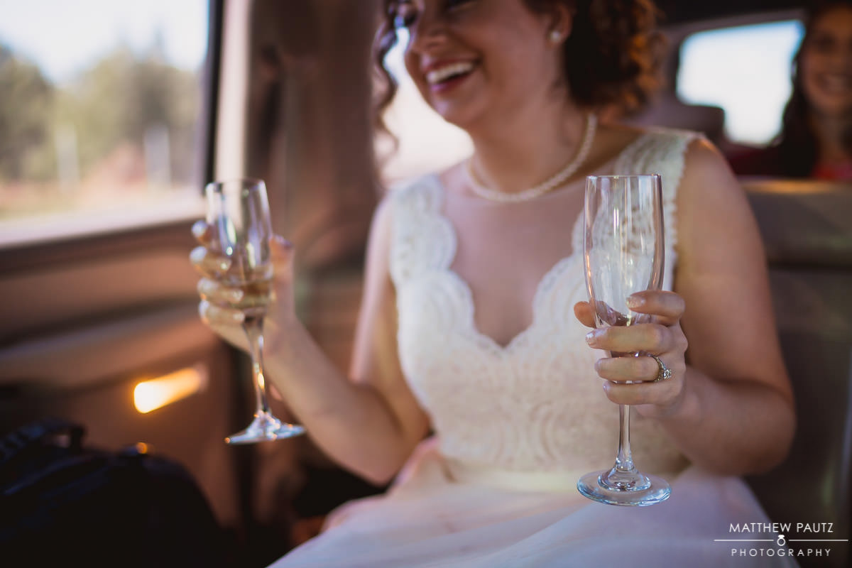 bride holding two drinks while taking limo to wedding